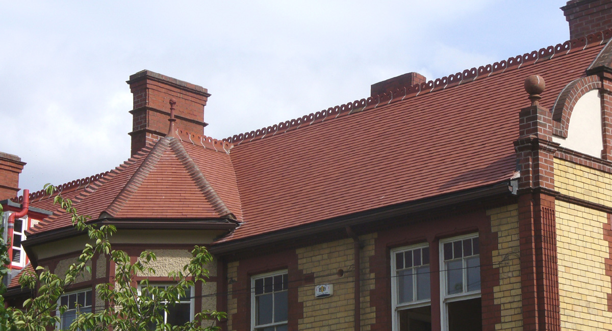 Red Smooth tiles with bonnet hips and matching ornamental ridge