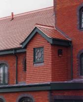 A reroofing project with Plum Red tiles with crested ridges made to match the originals